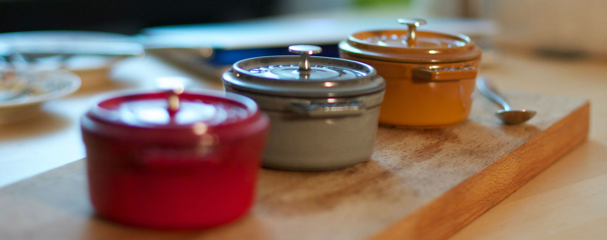 Three small enameled Dutch ovens on a chopping board
