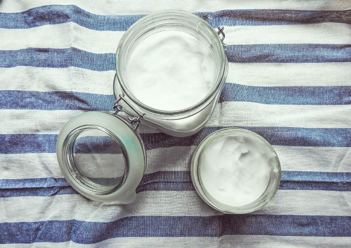 Glass jars filled with plain yogurt on a blue and white striped tablecloth