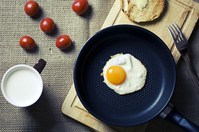 A fried egg in a frying pan surrounded by toast and cherry tomatoes