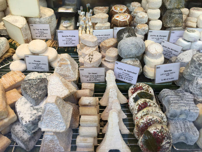 Selection of whole small cheeses on display in Paris cheese shop